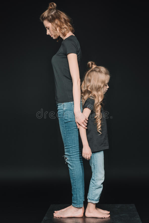 Side view of stylish daughter and mother standing back to back royalty free stock images