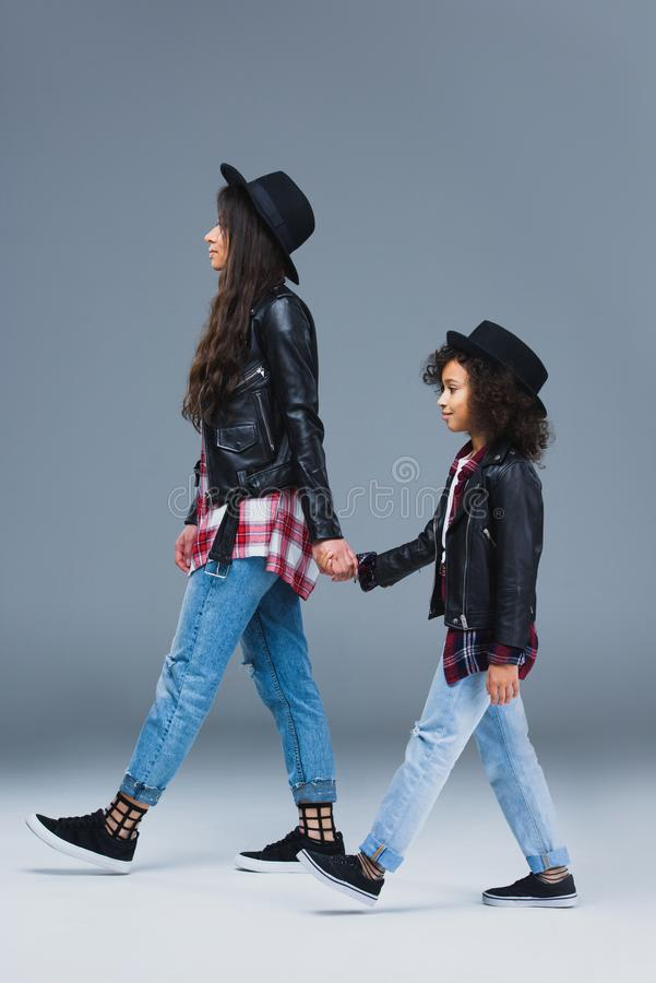 side view of stylish mother and daughter walking together and holding hands royalty free stock photo