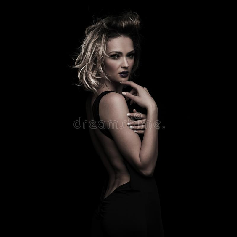Side view of stylish sensual woman flirting with parted lips. And holding her chin with her fingers while standing on black background royalty free stock photography