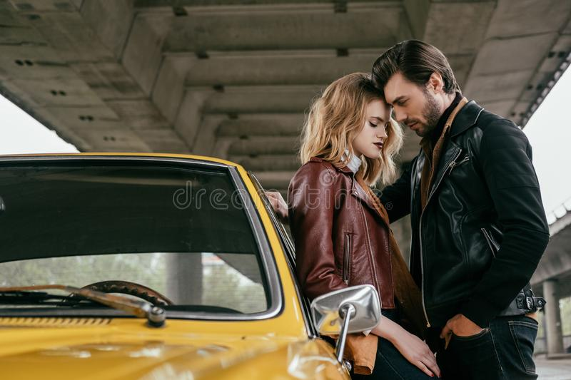 Side view of stylish young couple hugging near yellow retro car under. Bridge stock photography