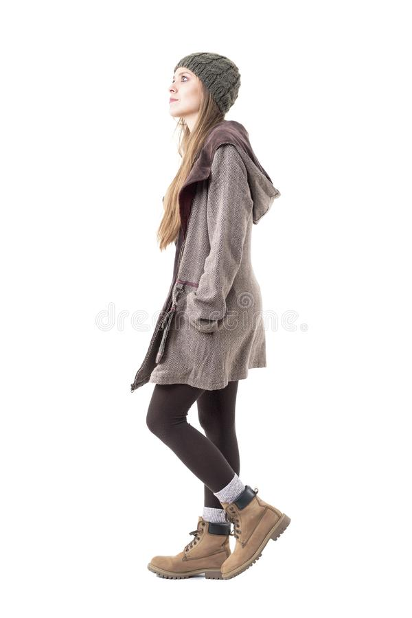 Side view of stylish young hipster woman wearing beanie and hooded coat walking and looking up. Full body isolated on white background royalty free stock photos
