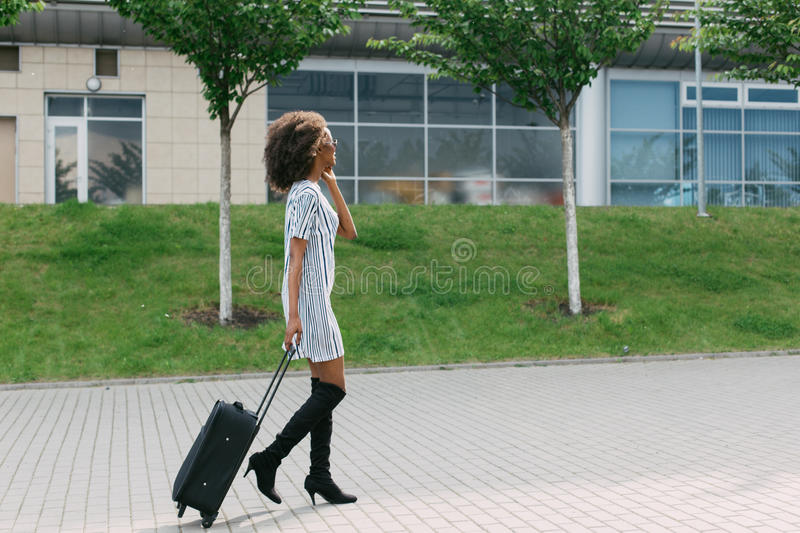Side view of the stylishly dressed afro-american woman holding the luggage while talking via mobile. Side view of the stylishly dressed afro-american woman royalty free stock image