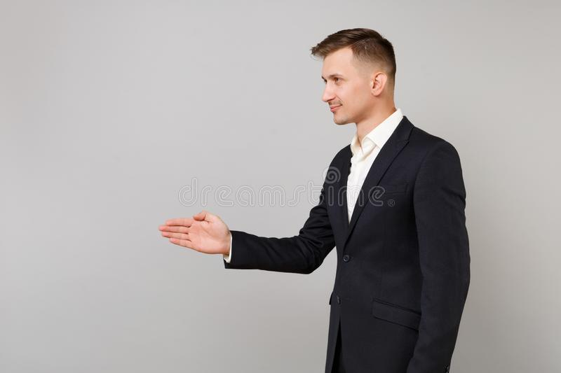 Side view of successful young business man in black suit standing with outstretched hand for greeting isolated on grey royalty free stock photo