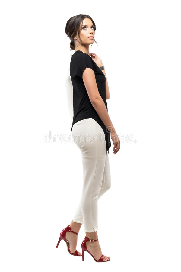 Side view of successful young business woman walking and carrying suit jacket looking up stock image