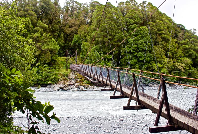 Side view of Suspension Bridge over River. E view of Suspension Bridge over River in New Zealand stock photos