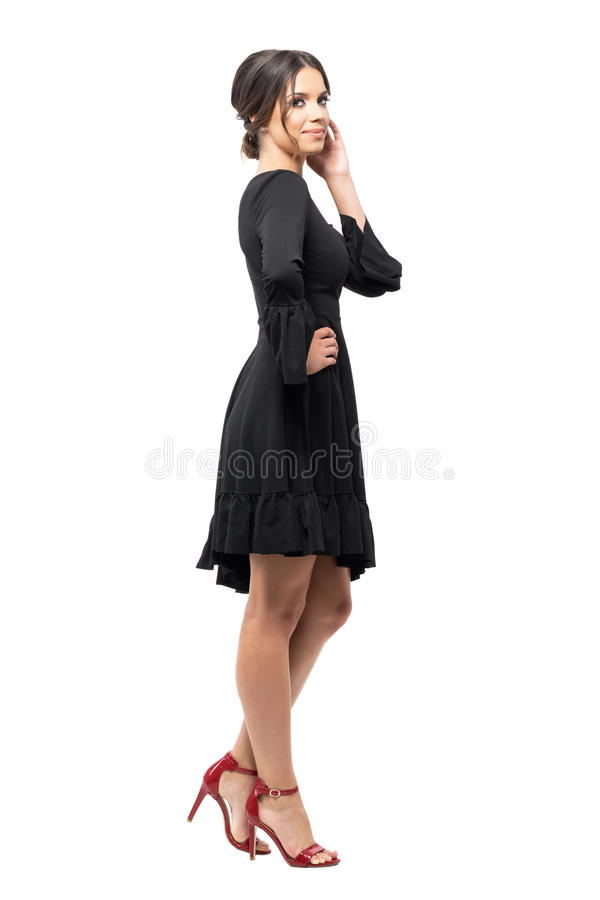 Side view of tanned Hispanic woman in black dress posing at camera touching hair. royalty free stock photography