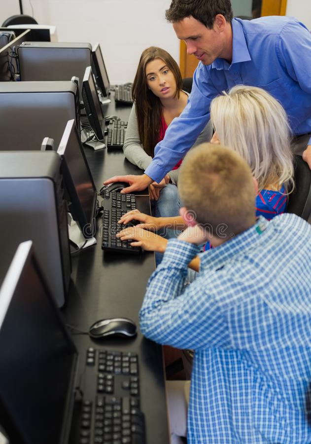 Teacher explaining to students in computer room. Side view of a teacher explaining to young college students in the computer room royalty free stock images