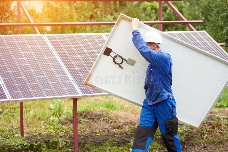 Installation of stand-alone exterior photo voltaic panels system. Renewable green energy generation. Side view of technician in protective helmet carrying big stock photos