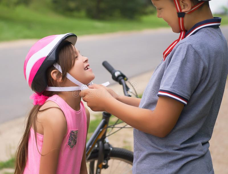 Children learn to ride bicycle in a park on summer day. Teenager boy helping preschooler girl to put on safety helmet royalty free stock photography