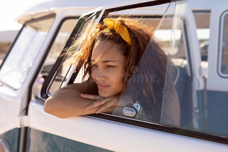 Young woman leaning on window of camper van at beach stock images