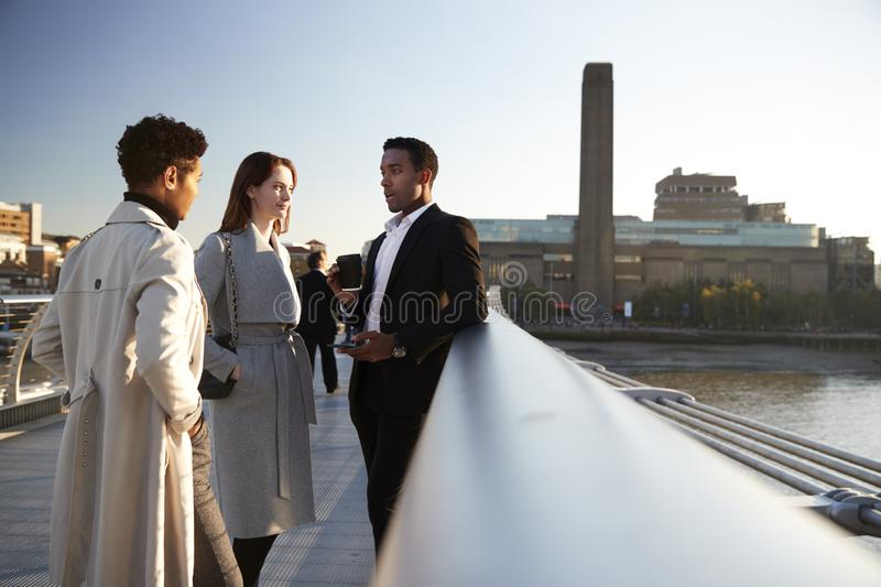 Side view of three millennial business colleagues stand talking on Millennium Bridge, London, selective focus stock images