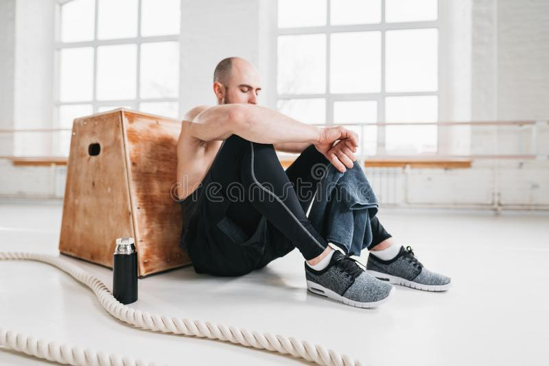 Side view of tired strong man sitting on box at gym royalty free stock photos