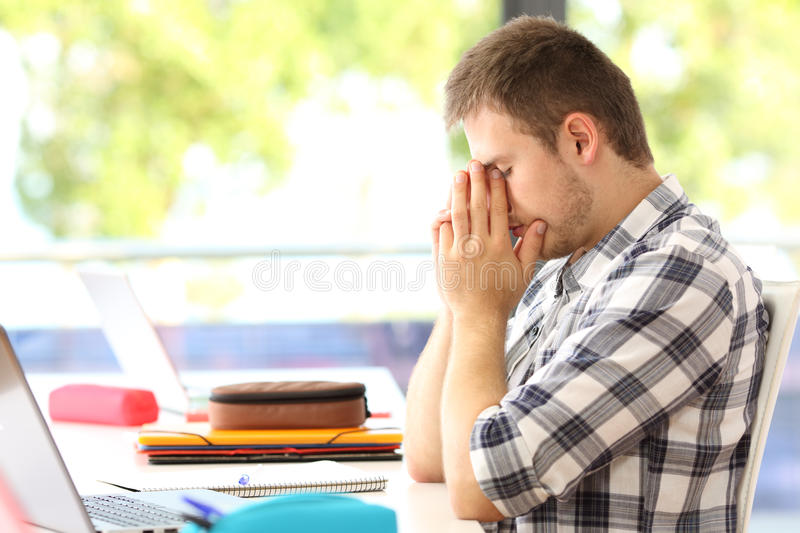 Tired student alone in a classroom royalty free stock photo