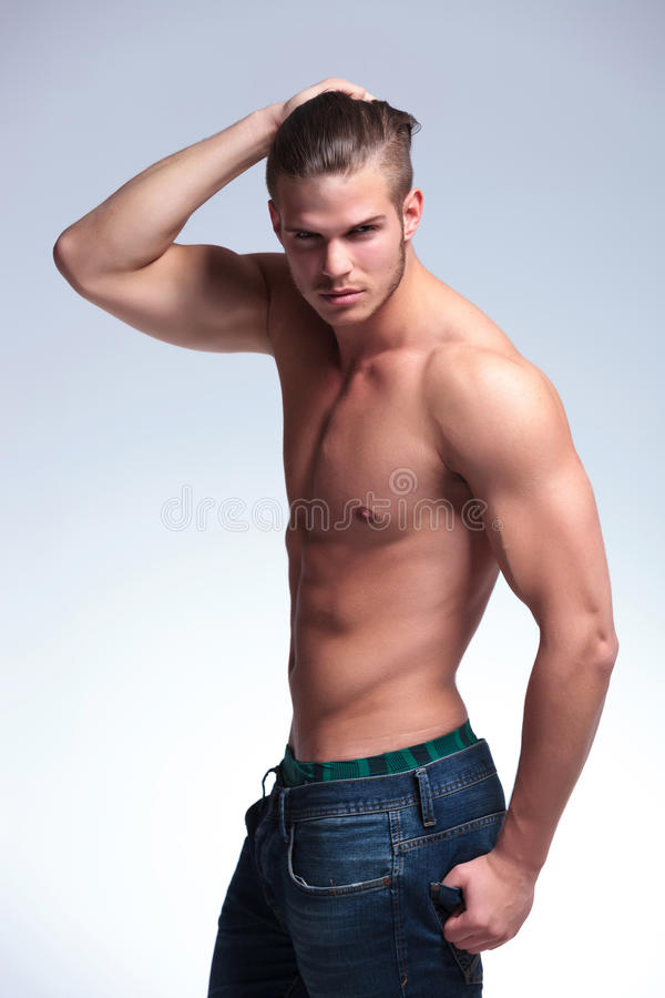 Side view of a topless young man. Side view of a young topless man standing with his hand in his hair and the other in his back pocket while looking into the stock image