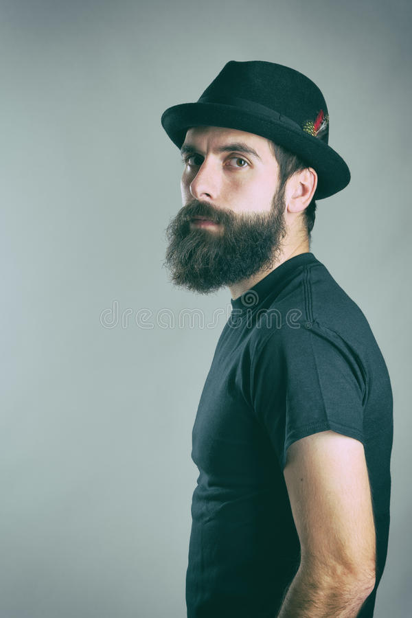 Side view of tough bearded macho man wearing black t-shirt and hat looking at camera. stock photos