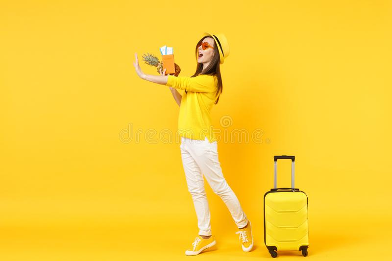 Side view of traveler tourist woman in hat hold passport tickets fresh pineapple fruit isolated on yellow orange. Background. Passenger traveling abroad on stock photography