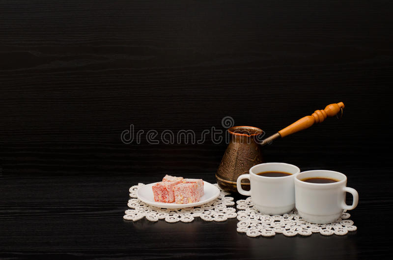 Side view of two cups of coffee on the lace napkins, Turkish dessert and pots. Side view of two cups of coffee on the lace napkins, dessert and Turkish pots on a royalty free stock photo