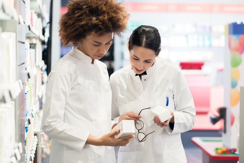 Side view of two dedicated pharmacists looking for the best medicine. Side view of two dedicated female pharmacists looking for the best medicine in the stock royalty free stock photography