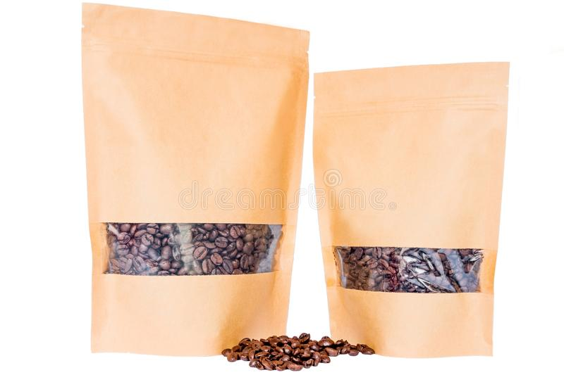 Side view of two kraft paper doypack stand up pouches with window and zipper filled with coffee beans on white background royalty free stock images