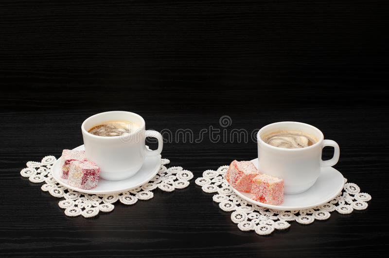 Side view of two mugs of coffee with ice-cream, Turkish delight on a saucer, on white lace napkins. stock photo