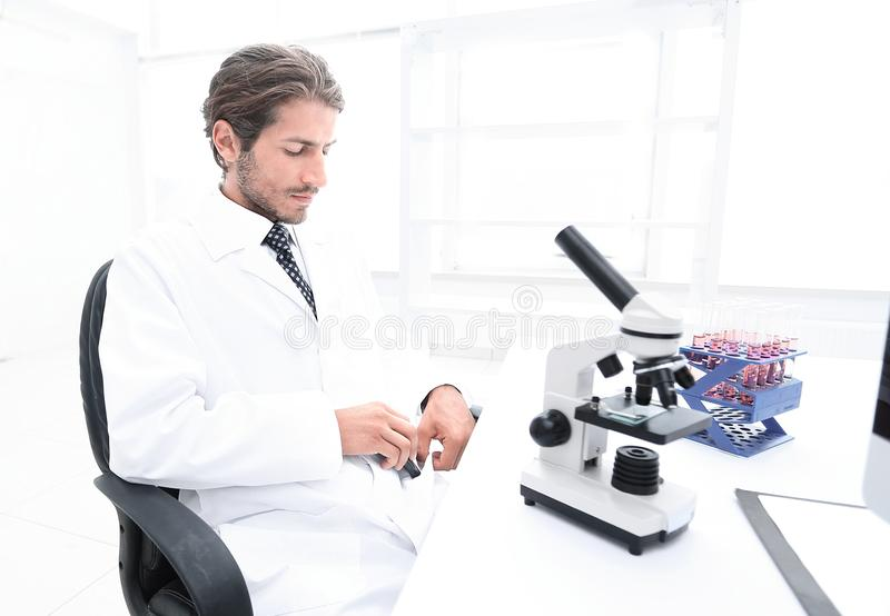 Side view of two scientists conducting a chemical experiment. Side view of a confident young women scientist, talking to her colleague in the laboratory stock images