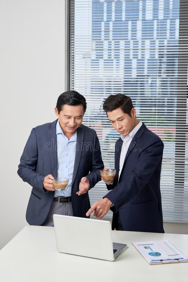 Side view of two serious young businessmen wearing black and blue suits drinking coffee and talking near big window stock image