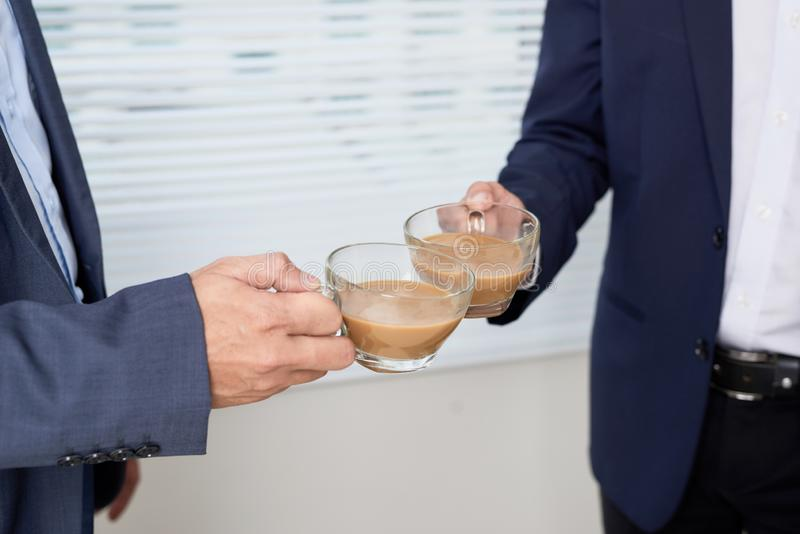Side view of two serious young businessmen wearing black and blue suits drinking coffee and talking near big window, confident stock images