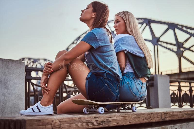 Side view of a two young hipster girls sitting on a skateboard and looking away on background of the old bridge at royalty free stock photos