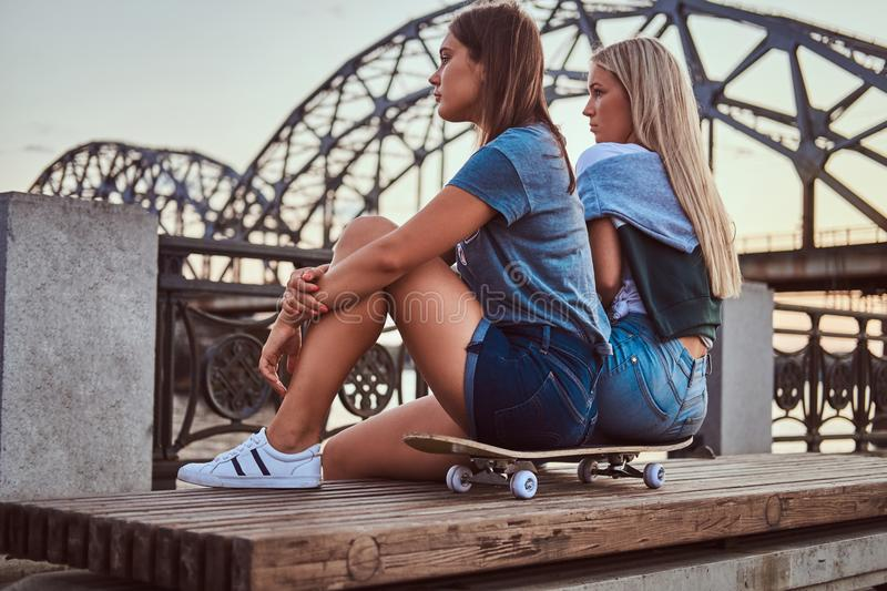 Side view of a two young hipster girls sitting on a skateboard and looking away on background of the old bridge at stock photo