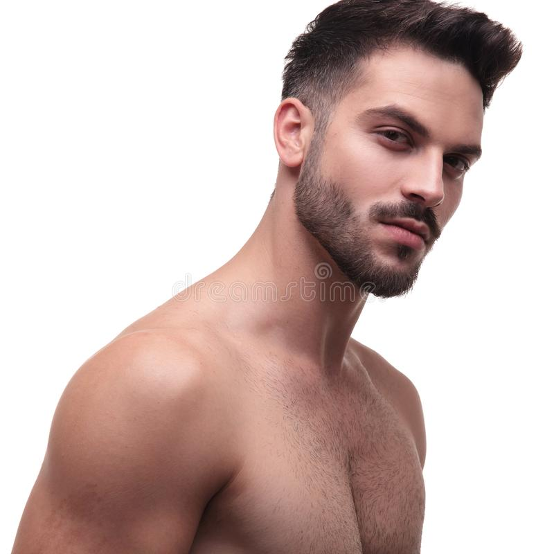 Side view of a undressed man with beard looking charming. On white background royalty free stock photography