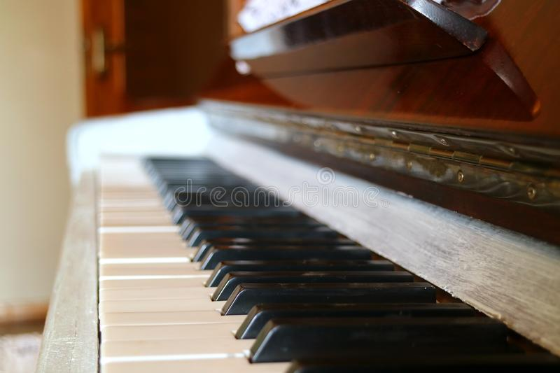 Side View of an Upright Piano`s Keyboard with Blurry Background royalty free stock photos