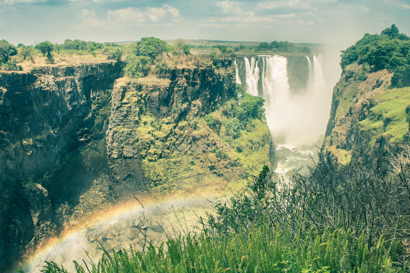 Side view of Victoria Waterfalls with rainbow natural effect stock images