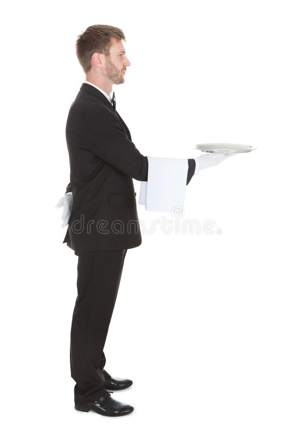 Side view of waiter holding empty tray stock image