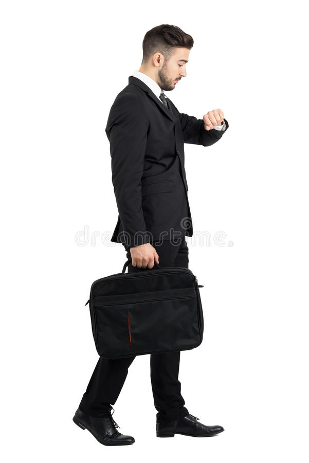 Side view of walking businessman checking hand watch time stock photos