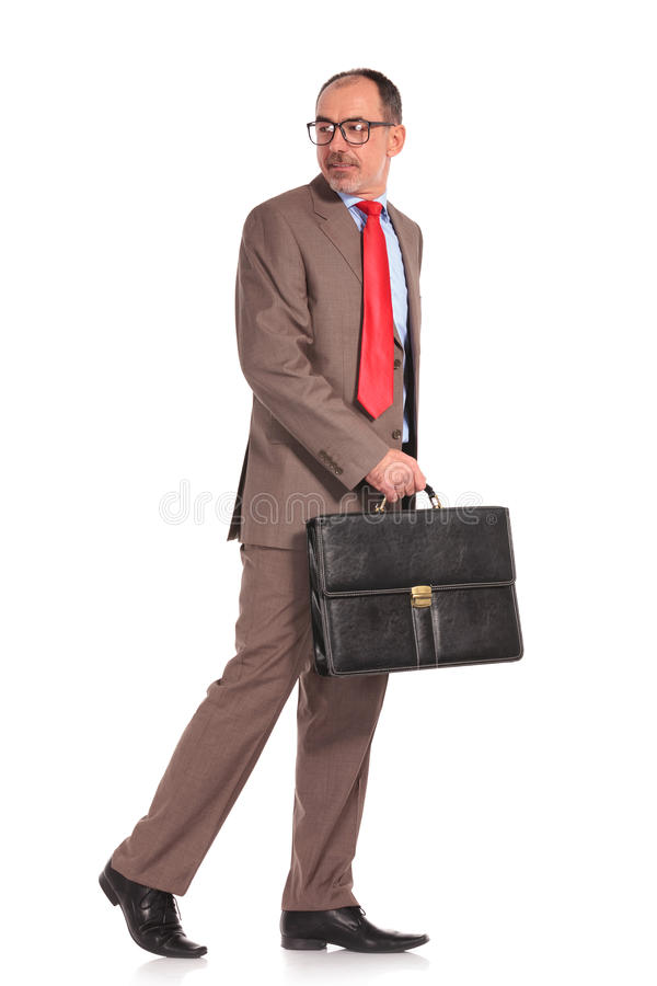 Side view of a walking businessman looking back stock images