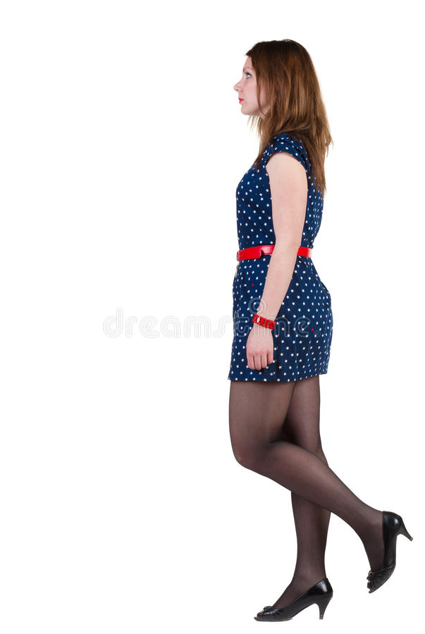 Side view of walking woman in blue dress royalty free stock image