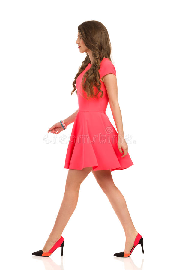 Side View Of Walking Woman In Pink Mini Dress stock photo