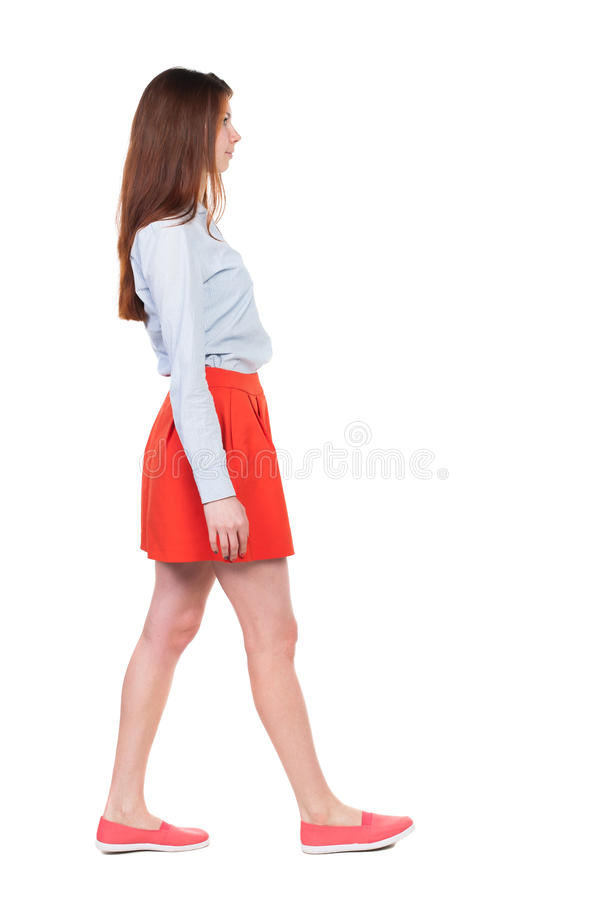 Side view of walking woman in red. royalty free stock photography