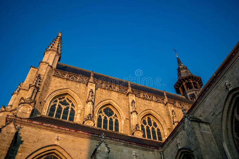 Church of Aalst, Belgium, beautiful afternoon. Side view, walls lit by falling sunlight of Collegiate Church Saint-Martin. Street image from below, clear blue royalty free stock photos