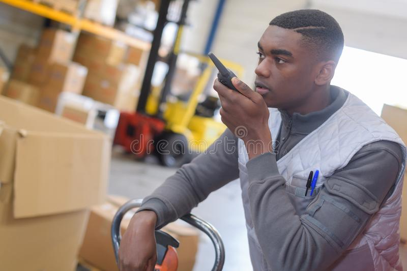 Side view warehouse worker using walkie talkie. Side view of a warehouse worker using walkie talkie royalty free stock photo