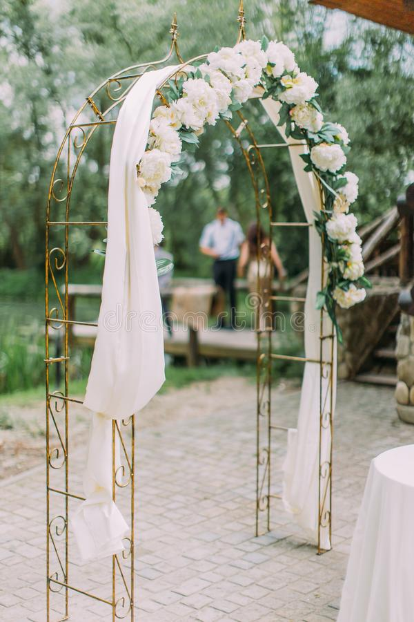 The side view of the wedding arch decorated with white flowers download the side view of the wedding arch decorated with white flowers stock photo junglespirit Gallery