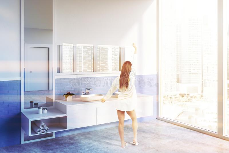 Side view of white bathroom with double sink woman. Woman in corner of modern bathroom with white and blue walls, concrete floor, double sink standing on wooden royalty free stock photo
