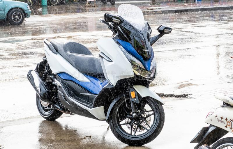 Side view of white-Blue 2018 Honda Forza 300 motorcycle parking on side walk in raining day stock photography