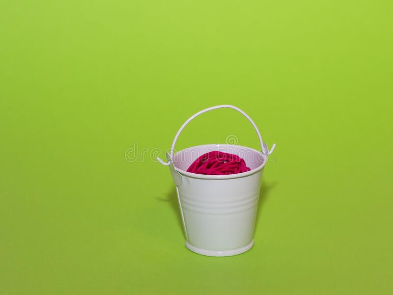 Side view of a white mini bucket in which lies a red rattan ball. Bucket stands on a green background stock images