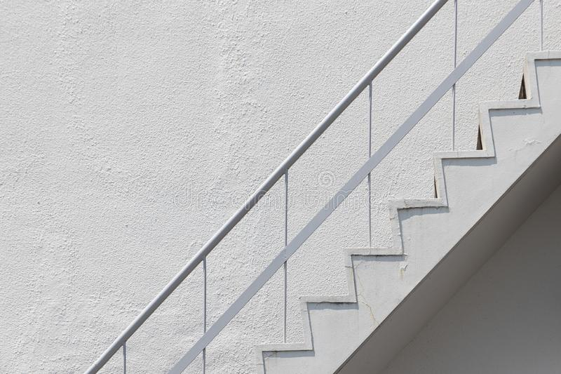 Side view of white outside fire escape emergency staircase with metal handrail railing and concrete wall stock image