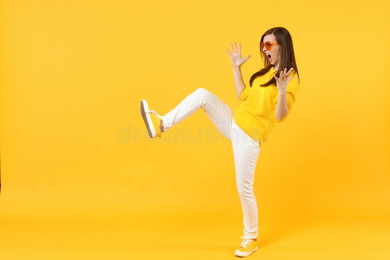 Side view of wild young woman in casual clothes, heart glasses showing palms kicking something isolated on yellow orange royalty free stock photos