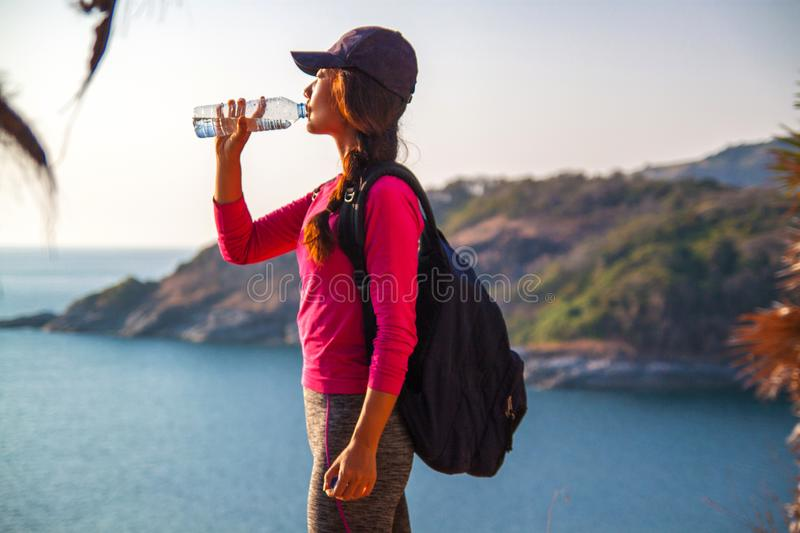 Side view of woman with backpack and a bottle of water looking at sea while sitting on hill against sky . stock photos