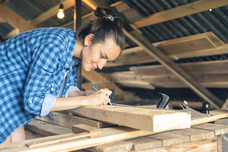 Side view of a woman carpenter draws on a wooden Board cut line royalty free stock images