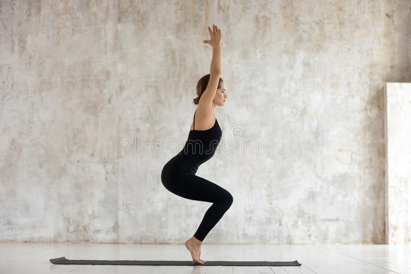 Side view woman doing Chair Pose Utkatasana yoga indoors royalty free stock photography