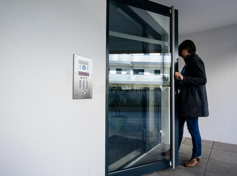 Side view of woman entering apartment building intercom access. Side view of woman entering modern apartment building with glass door and modern intercom system stock photos